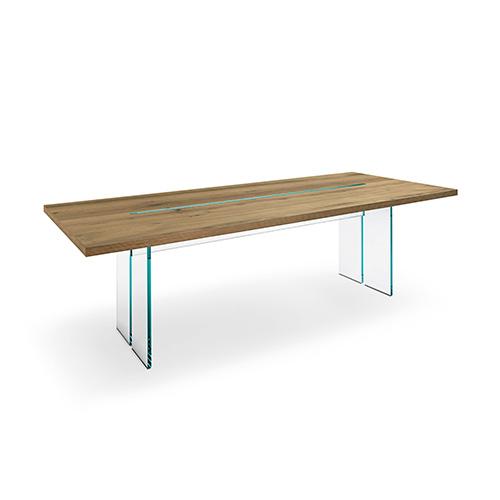 Da Fiam il tavolo LLT wood (Long Long Table) dello studio Dante O. Benini & Partners: la base di vetro è inserita nella fresata del piano in legno per creare un gioco di luce e trasparenza