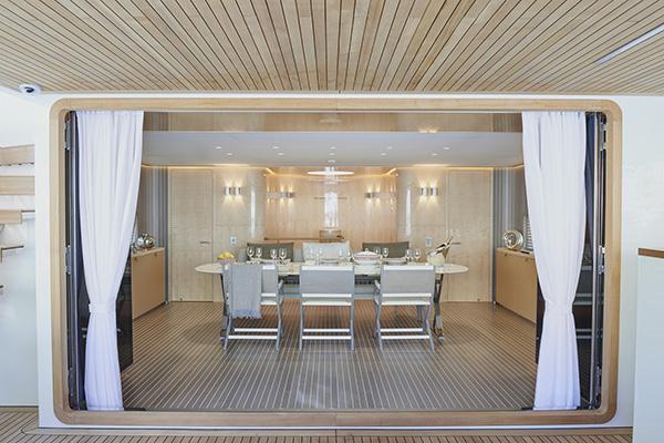 Sul ponte superiore spicca Pathos, il grande tavolo da cucina firmato Maxalto. È circondato dalle sedie Emily di Flexform