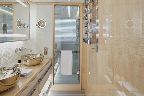 Il bagno padronale del ponte principale si caratterizza per gli infissi in legno d'acero e per il rivestimento in mosaico Honeycomb Mutina. I rubinetti sono firmati da Citterio per  Axor