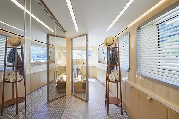 La cabina armadio nel ponte principale: il muro è ricoperto di specchi su misura che coprono il guardaroba di B&B Italia e riflettono la luce del sole che proviene dall'esterno. Sul retro, un elegante vestiere in legno e pelle di Hermès