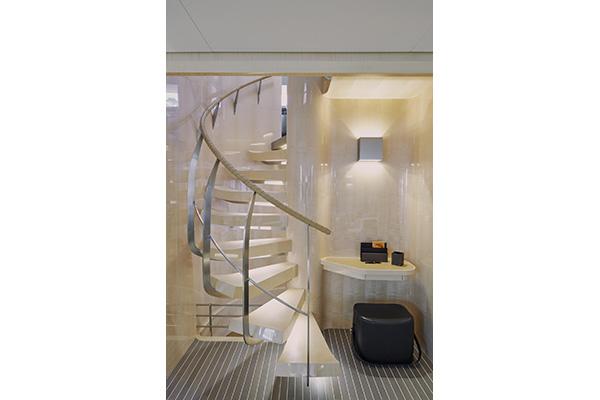 Le scale superiori sono circondate da infissi in acero. In un piccolo angolo c'è lo spazio per una scrivania, un pouf Hermès e una lampada a muro di Viabizzuno