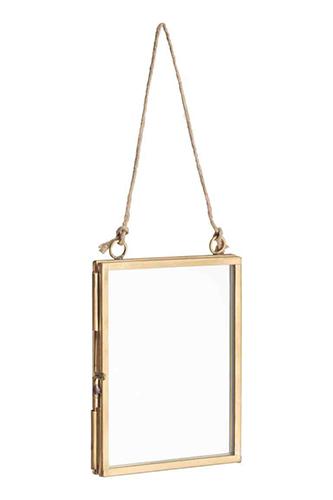 Altra proposta H&M Home: cornice in vetro trasparente e metallo. Con chiusura scorrevole su un lato e due occhielli con cordino per appenderla