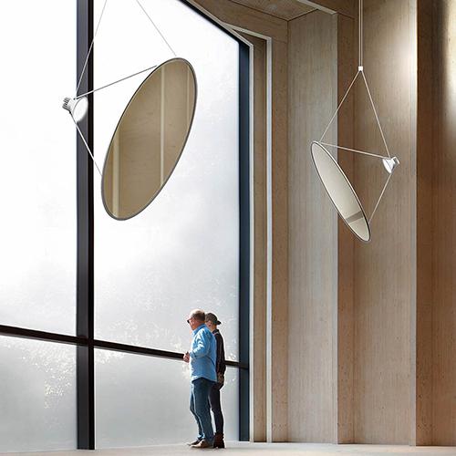"""Sol_03, il progetto di Luceplan, è """"come una vela solare"""", racconta il designer norvegese Daniel Rybakken. """"All'interno di un profilo circolare in alluminio è teso un film bianco traslucido o una membrana a specchio metallizzata. Una fonte luminosa molto potente proietta un fascio di luce sul grande e leggerissimo disco, diffondendo e riflettendo la luce"""""""