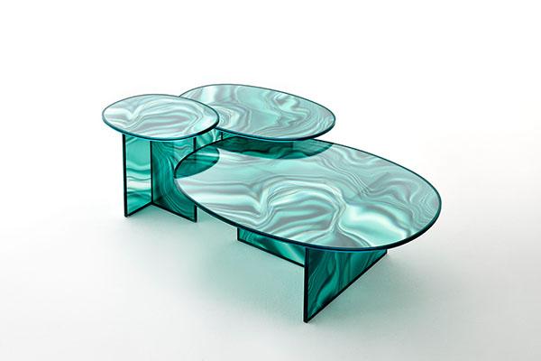 La loro decorazione, sfumata e irregolare, riprende le colorazioni e le venature del marmo: sono i tavoli alti e bassi in cristallo trasparente di Patricia Urquiola per Glas