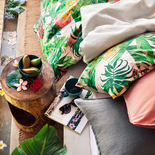 """Una piccola oasi naturale anche in camera da letto con i cuscini e il copriletto di <a href=""""http://www2.hm.com/it_it/home.html"""">H&M Home</a> che citano fiori e piante esotiche"""