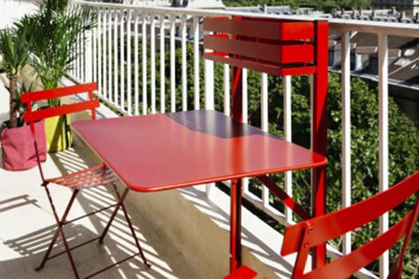 Da Fermob, Bistro, il tavolino per organizzare pranzi e cene in mini balconi. Si aggancia alla ringhiera e nella parte superiore ha un vano per contenere i vasi con i fiori