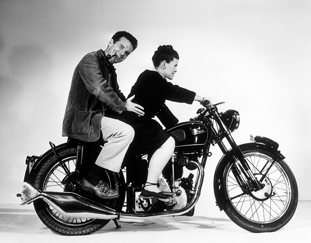 An Eames Celebration. Charles e Ray Eames in posa sulla motocicletta Velocette, 1946