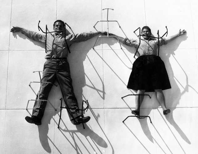 An Eames Celebration. Charles and Ray in posa con basi in metallo delle sedie