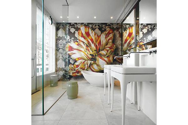 Divergenze di gusti tra marito e moglie: l'oggetto del contendere è lo stile dei rivestimenti. Lei sogna un bagno personalizzato con pattern preziosi e luminosi, lui preferirebbe una soluzione più neutra. Decidono per piastrelle chiare a pavimento e per un decoro più ricco su una sola parete. Come nell'ambientazione proposta da Bisazza, con grande fiore a mosaico su disegno del designer olandese Marcel Wanders