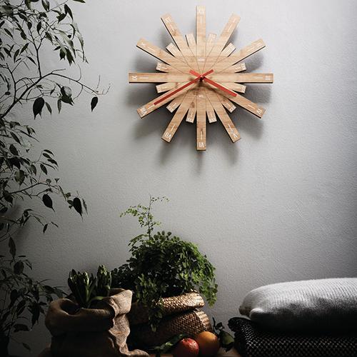 """Firmato da Michele De Lucchi, <em>Raggiante </em> di <a href=""""http://www.alessi.com"""">Alessi</a> </span><span class=""""s2"""">appare come un sole da cui si dipartono 24 raggi che scandiscono le ore. Le lancette, in alluminio arancione, risaltano sul colore caldo del legno (180 euro)"""