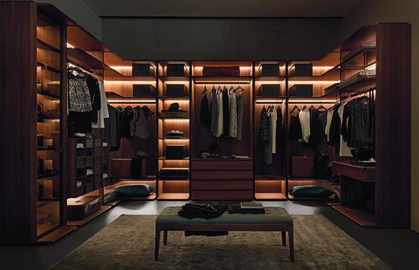 My suite è la cabina armadio componibile firmata Porada: in noce canaletto, ha dettagli in metallo e maniglie in maglia intrecciata. Personalizzabile grazie all'aggiunta di accessori e illuminazione led