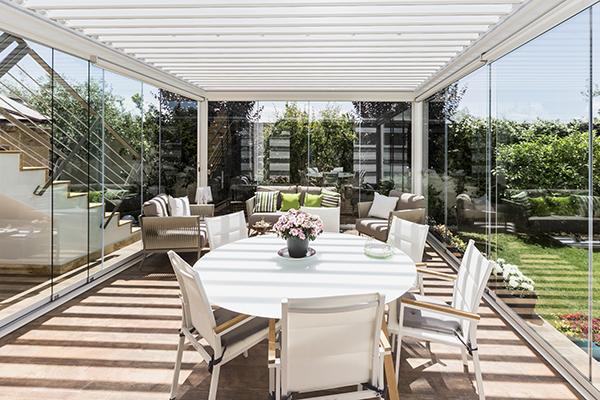 Sfruttare un'area del giardino in ogni mese dell'anno e realizzare uno spazio areato d'estate e protetto d'inverno, con la pergola bioclimatica Med Twist di Gibus. Qui nella versione addossata, larga 4 metri e 50 centimetri e profonda 5 metri e 50, con lame orientabili e vetrate scorrevoli