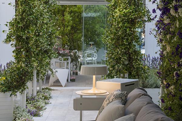 Da Frigerio, la pergola Flap one, con lame motorizzate, luci a led e struttura in alluminio. Alcune pareti perimetrali sono decorate con le piante ornamentali come Verbena e Vinca