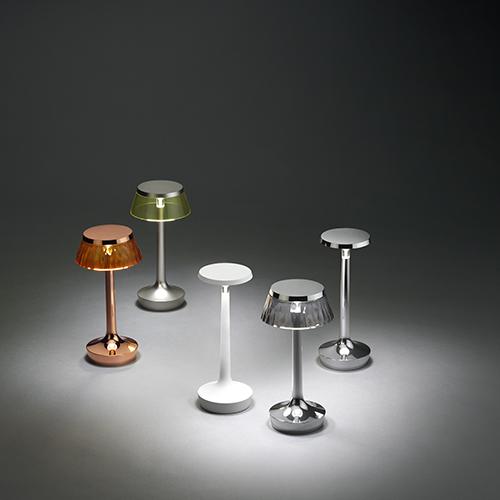 """<em>Bon Jour Unplugged </em>di <a href=""""https://flos.com"""">Flos</a> è una lampada da tavolo senza fili e personalizzabile. La sorgente luminosa si ricarica tramite usb ed è possibile regolare il flusso scegliendo tra quattro intensità. Le corone sono intercambiabili e disponibili in diverse finiture e materiali: plastica, tessuto plissé o rafia naturale (dal 250 a 270 euro, corone accessorie da 15 a 40 euro)"""