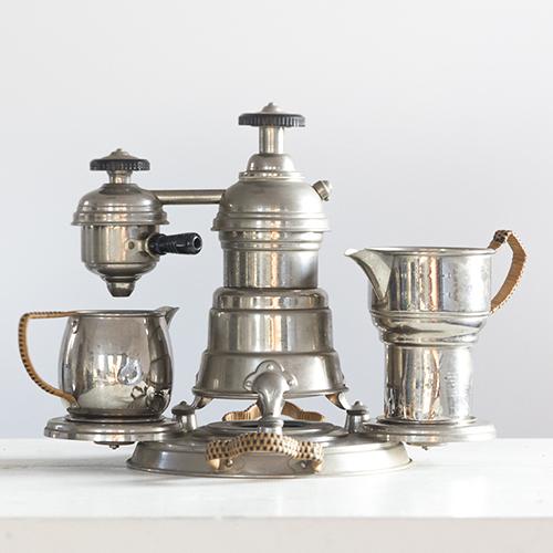 Gruppo tavola <em>Velox</em>, anni Sessanta, composto da una caffettiera alimentata elettricamente, da una lattiera e da una tazza per raccogliere il caffè in uscita - vassoio con manici per il trasporto a tavola, decorati con midollino intrecciato a mano in tre colori