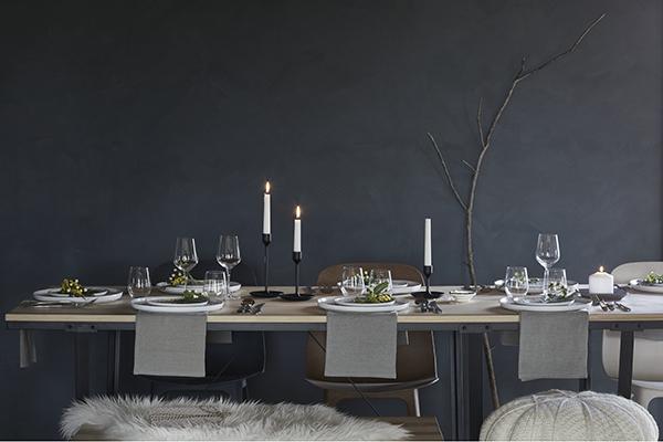 """<em>La tavola minimale</em> -Se preferite uno stile essenzialesenza dimenticare l'ispirazione natalizia. <a href=""""http://www.ikea.com"""">Ikea</a> sostituisce la classica tovaglia con più runneradagiati su un lungo tavolo in legno e dona un tocco naturalee festoso grazie alle candele e ai rametti di pino al centro di ciascun piatto"""