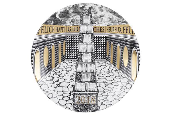 """Il famoso <em>Piatto Calendario</em> di <a href=""""http://www.fornasetti.com/it"""">Fornasetti</a> è giunto alla cinquantunesima edizione. Per il 2018 Barbara Fornasetti ha disegnato un obelisco che si erge al centro di un cortile circondato da tre edifici. Realizzato in porcellana e oro si può acquistare a Milano presso il Fornasetti Store"""