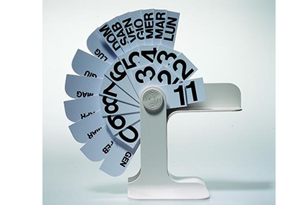 """Quando si parla di calendari non può mancare <em>Timor</em> di Enzo Mari. Progettato nel 1966 per <a href=""""http://www.danesemilano.com"""">Danese Milano</a> è semplice e dura per sempre. Si caratterizza per l'apertura a ventaglio: i fogli ruotano su un perno e indicano mese, numero e giorno della settimana <p class=""""p1""""></p>"""