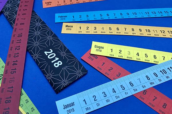 """Il <em>Ruler Calendar </em>di Fabriano è l'ideale per l'home office: un astuccio contiene 12 righelli per 12 mesi. Disponibile in 4 lingue, la versione inglese presenta un lato in centimetri e un lato in pollici, le altre versioni sono tutte in centimetri. Si può acquistare <a href=""""https://www.fabrianoboutique.it/ruler-calendar-2018.html"""">qui</a>"""