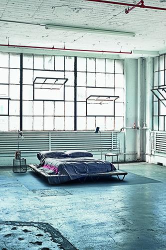 Un'enorme finestra panoramica illumina la camera da letto minimale in cui spiccano le tubazioni lasciate a vista e le pareti grezze