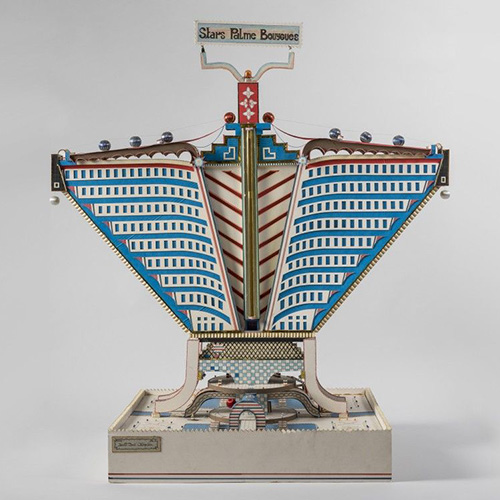 """NEW YORK - Il <a href=""""http://www.moma.org"""">MoMa</a>, rende omaggio a Bodys Isek Kingelez, l'artista originario della Repubblica Democratica del Congo, scomparso nel 2015. La retrospettiva """"City Dreams"""" è la prima in America che spiega il lavoro di Kingelez e lo fa abbracciando tutta la sua carriera. Fino al 1 gennaio in mostra sculture di edifici immaginari e ambiziose soluzioni abitative, tra cui il modellino <em>Stars Palme Bouygues</em> del 1989 (nella foto di Vincent Everarts Photography Bruxelles), con l'obiettivo di dare vita a un «mondo migliore e più pacifico», come affermò l'artista"""