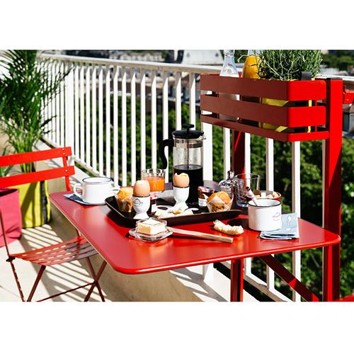 """Il tavolo <em>Bistro</em> di <a href=""""http://Fermob"""">Fermob</a> si aggancia alle inferriate di tutte le forme e misure. Il piano d'appoggio  ribaltabile quando è chiuso occupa pochissimo spazio così da poter vivere il balcone senza problemi, specie quelli più stretti"""