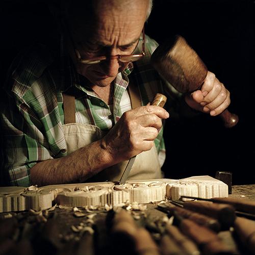 Bruno Barbon impegnato nell'intaglio del legno nella sua bottega di Venezia attiva dal 1960; è uno dei protagonisti di Homo Faber, nella mostra fotografica Venetian Way con gli scatti di Susanna Pozzoli (foto Susanna Pozzoli)