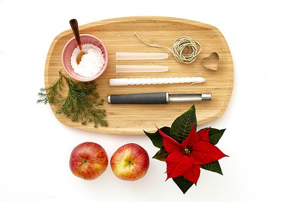 Prendiamo l'occorrente: due mele rosse, una Stella di Natale, un vassoio, del verde, una candela, dello zucchero a velo, due provette da orchidea, un levatorsolo, un filo, delle forbici e uno stampino per biscotti (foto Stars For Europe)