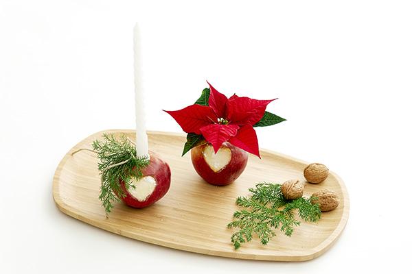 Fase 5: Inserire una candela in una delle mele, riempire la provetta nell'altra mela con dell'acqua e inserire una Stella di Natale recisa. Per fermare il flusso di linfa lattea, tenere gli steli tagliati immersi nell'acqua a 60 ° C per alcuni secondi, quindi immergerli in acqua fredda. Disporre tutto sul vassoio, aggiungendo altre decorazioni (foto Stars For Europe)