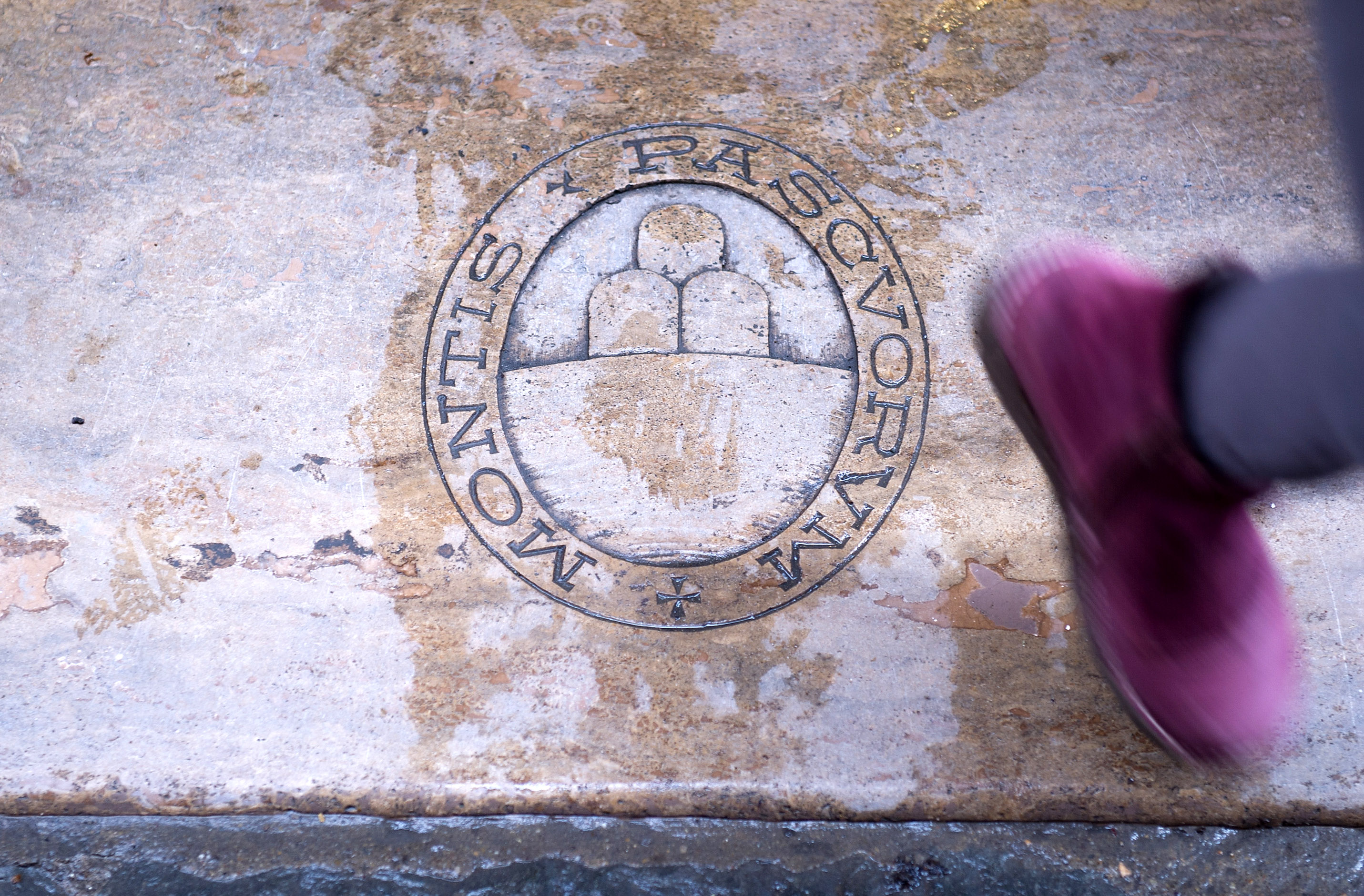 SIENA, ITALY - APRIL 05: A woman steps on a Banca Monte Paschi paving stone whilst leaving a branch in the city centre on April 5, 2013 in Siena, Italy. The Bank of Italy has today ordered former top executives of MPS to pay a total of 5 million Euros (GBP £4.2 million) in fines for lack of controls over risky trades at the bank. (Photo by Marco Secchi/Getty Images)
