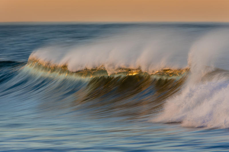 perfect wave breaking in sunrise light