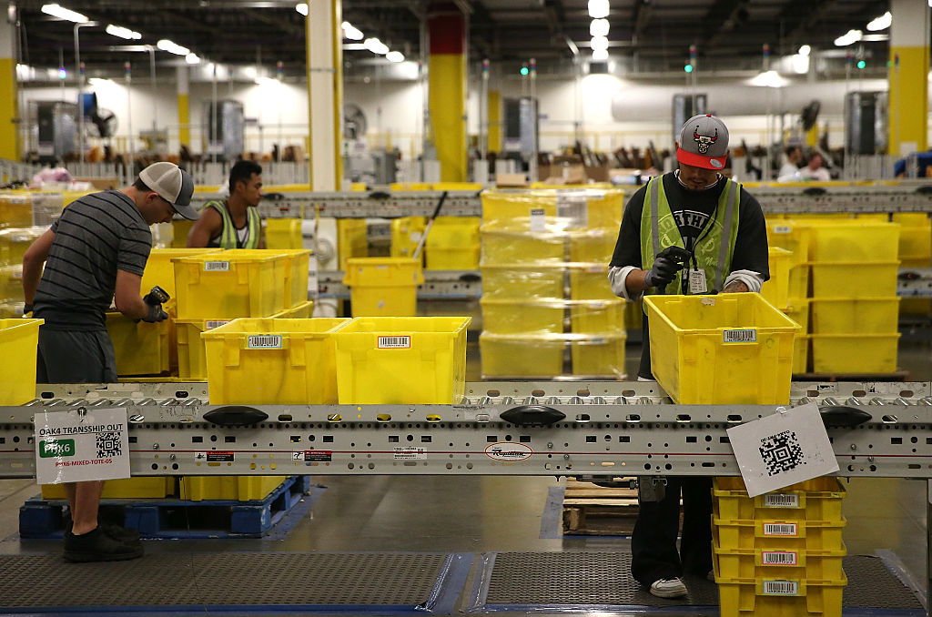 TRACY, CA - JANUARY 20: Amazon.com workers pack orders at an Amazon fulfillment center on January 20, 2015 in Tracy, California. Amazon officially opened its new 1.2 million square foot fulfillment center in Tracy, California that employs more than 1,500 full time workers as well as 3,000 Kiva robots that can fetch merchandise for workers and are capable of lifting up to 750 pounds. Amazon is currently using 15,000 of the robots spread over 10 fulfillment centers across the country. (Photo by Justin Sullivan/Getty Images)