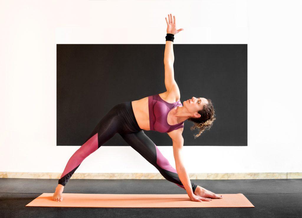 Young woman doing a triconasana yoga pose