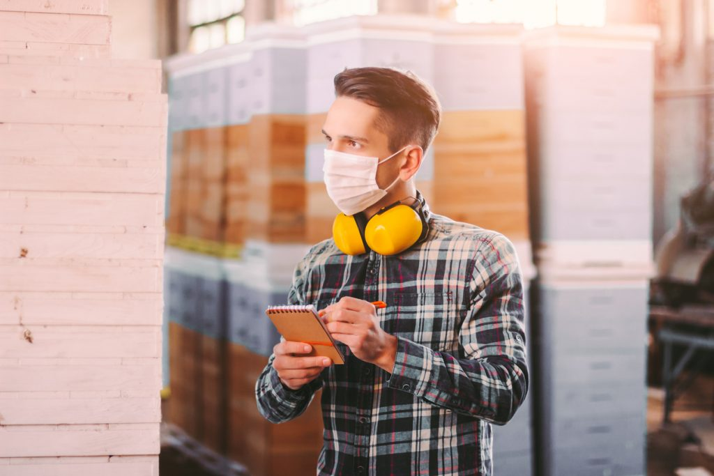 Man supervisor inspecting warehouse during COVID-19 quarantine