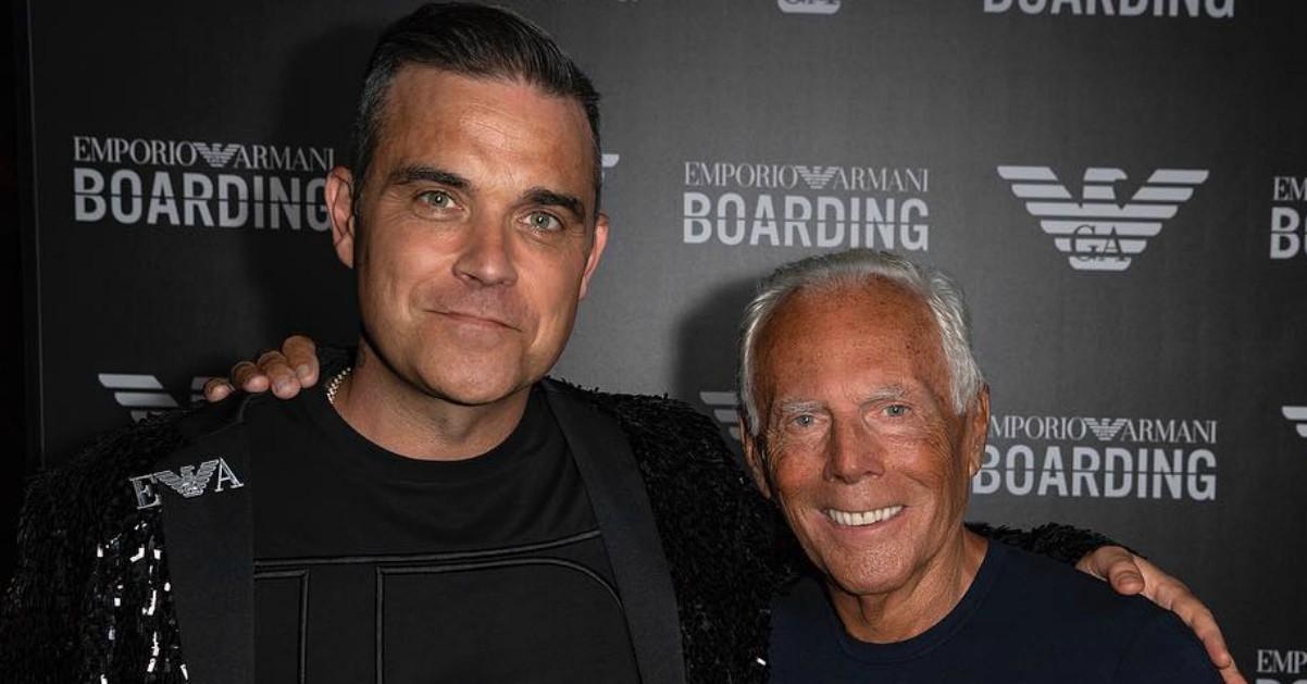 Robbie Williams show alla Milano Fashion Week: canta per Armani con gonna e paillettes