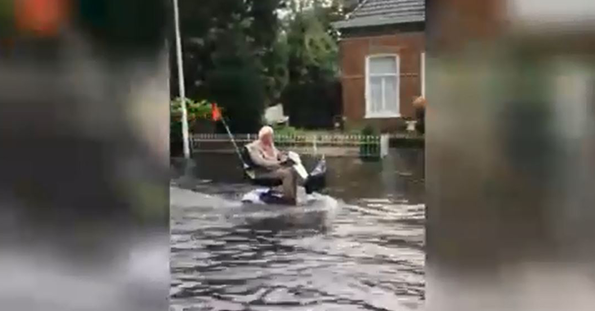 L'inondazione non spaventa l'anziano: attraversa la strada con la carrozzina elettrica