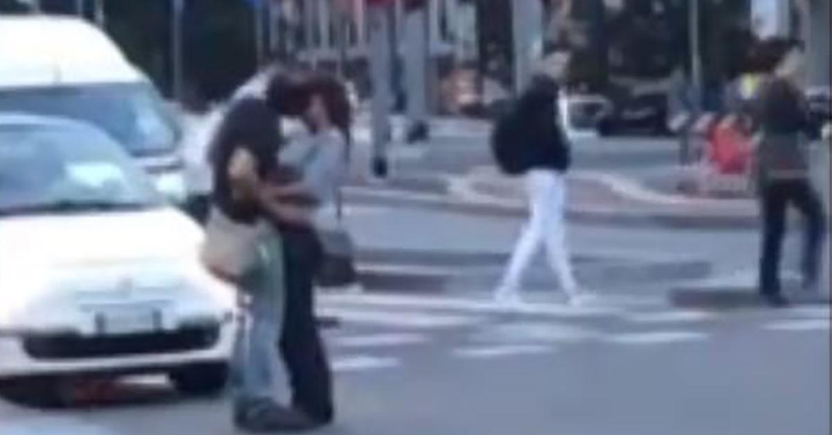 Milano, la coppia si lascia andare in un lungo bacio in mezzo alla strada bloccando il traffico