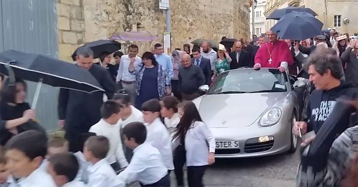 Malta, Prete sfila su una Porsche trainata da 50 bambini: è polemica