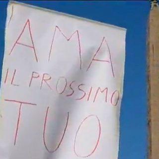 """In piazza col cartello """"Ama il prossimo tuo"""": trascinato via"""