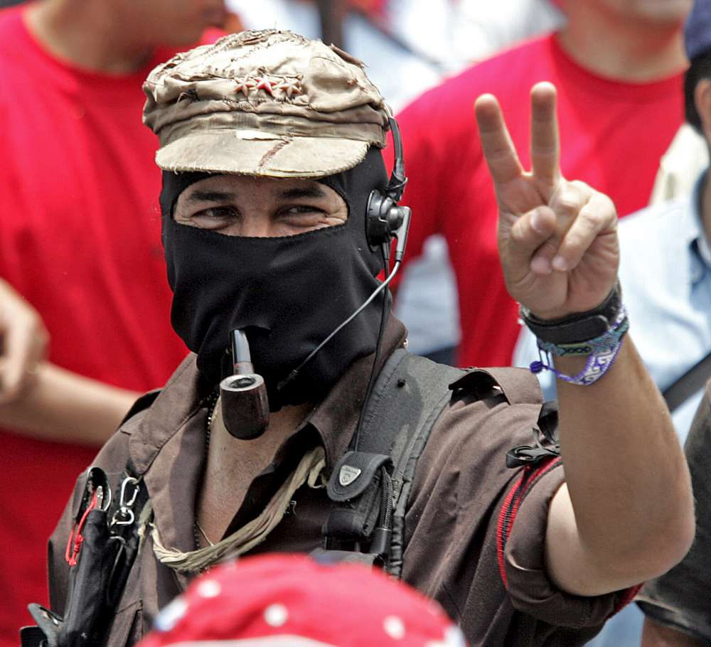 """The leader of the Zapatista National Libertation Army (EZLN), Sub Comandante Marcos (C), flashes the """"v"""" sign as he takes part in a march along the streets of the Mexico City, 01 May, 2006 during the celebrations for May Day. From rural mountainous Nepal to the industrial heartland of Germany, workers took to the streets around the world on Monday in largely peaceful May Day demonstrations for labour rights, as immigrants in the United States prepared a jobs boycott. AFP PHOTO / Luis ACOSTA"""