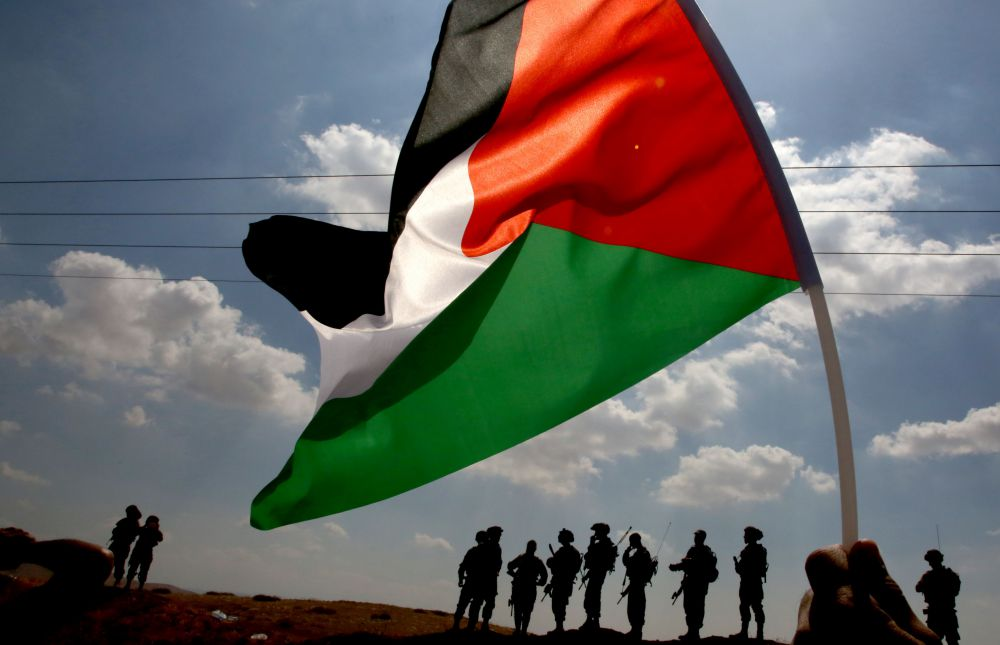 A Palestinian demonstrator holds his national flag as Israeli securty forces stand guard during a protest against the expropriation of Palestinian land in the village of Tamun, near Nablus, in the Israeli occupied West Bank, on September 27, 2017.  / AFP PHOTO / JAAFAR ASHTIYEH        (Photo credit should read JAAFAR ASHTIYEH/AFP/Getty Images)