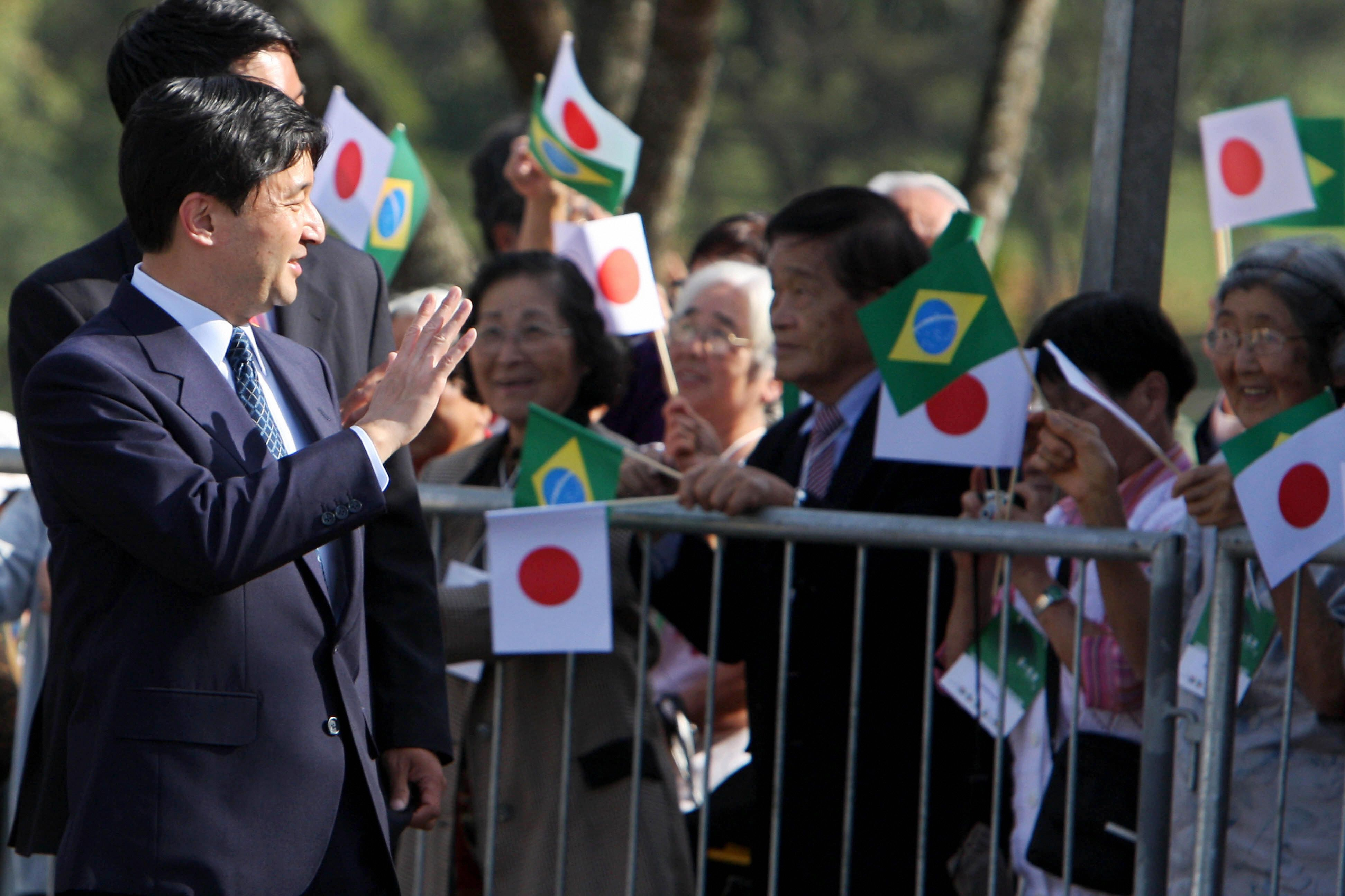 Japan's Crown Prince Naruhito (L) waves to the crowd during a ceremony in honour of Japanese immigrants in Sao Paulo on June 20, 2008. Prince Naruhito is in Brazil on a 12-day visit to take part in the celebrations marking the 100th anniversary of Japanese immigration to the South American nation, where exists the largest Japanese community outside of Japan. AFP PHOTO/Nelson ALMEIDA. (Photo credit should read NELSON ALMEIDA/AFP/Getty Images)