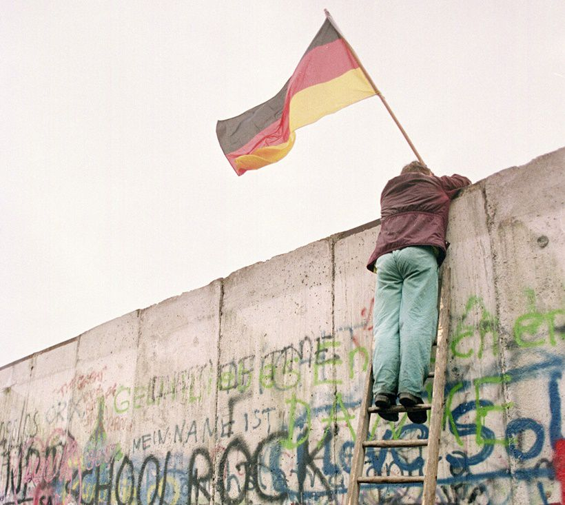 A picture taken 11 November 1989 shows a West Berliner preparing to hand over a FRG flag to East German Vopo policemen through a portion of the fallen Berlin Wall near the Brandenbourg Gate. Two days before, Gunter Schabowski, the East Berlin Communist party boss, declared that starting from midnight, East Germans would be free to leave the country, without permission, at any point along the border, including the crossing-points through the Wall in Berlin. As the 45th anniversary of the building of the Berlin Wall nears, a row has broken out about the still unknown number of people who were shot while trying to scale communism's ultimate symbol. Researchers said they have confirmed beyond a doubt 125 cases where people were killed while trying to make it across the wall that went up overnight on August 13, 1961 and divided Berlin for the next 28 years.    AFP PHOTO    GERARD MALIE        (Photo credit should read GERARD MALIE/AFP/Getty Images)
