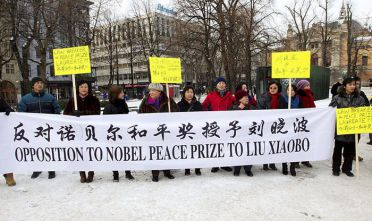 "A small group of pro-Chinese authorities protesters gather behind a banner during a demonstration in Oslo on December 10, 2010 to voice opposition to the awarding of this year's Nobel Peace Prize to jailed Chinese dissident Liu Xiaobo. China lashed out on December 10 at the ""political theatre"" of the Nobel committee, saying its awarding the 2010 Peace Prize to jailed dissident Liu Xiaobo was a product of a ""Cold War mentality"".    AFP PHOTO / SCANPIX NORWAY / Morten Holm    -- NORWAY OUT -- (Photo credit should read HOLM, MORTEN/AFP/Getty Images)"