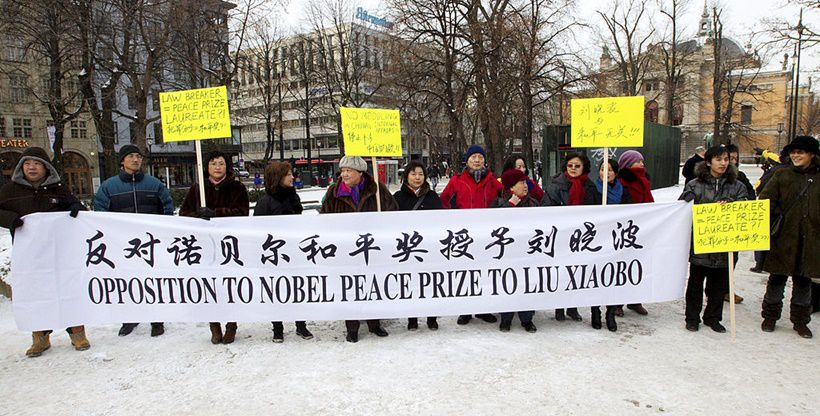 """A small group of pro-Chinese authorities protesters gather behind a banner during a demonstration in Oslo on December 10, 2010 to voice opposition to the awarding of this year's Nobel Peace Prize to jailed Chinese dissident Liu Xiaobo. China lashed out on December 10 at the """"political theatre"""" of the Nobel committee, saying its awarding the 2010 Peace Prize to jailed dissident Liu Xiaobo was a product of a """"Cold War mentality"""".    AFP PHOTO / SCANPIX NORWAY / Morten Holm    -- NORWAY OUT -- (Photo credit should read HOLM, MORTEN/AFP/Getty Images)"""
