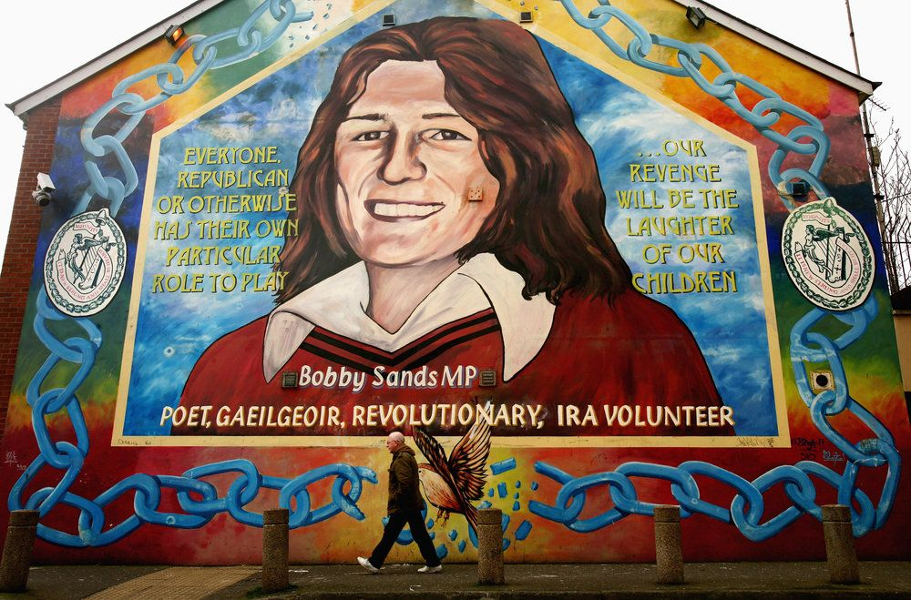 BELFAST, UNITED KINGDOM - MARCH 14: A man walks past the Bobby Sands mural, in the Falls road area of Belfast , Sands was the first hunger striker to die in the 1981 hunger strike, March 14, 2009  in Northern Ireland. Communities in Northern Ireland remain adamant that they do not want to be dragged back into conflict following last weeks attacks.  (Photo by Jeff J Mitchell/Getty Images)