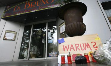 """Flowers and candles are laid down in front of the Italian restaurant """"Da Bruno"""" in Duisburg, western Germany, where worked six men shot dead 15 August 2007 in a mafia vendetta.. Italy's Interior Minister Giuliano Amato said the victims, six men ranging from 16 to 38 years old, were caught up in a feud between powerful mafia families in the Calabria region of southern Italy. (plate reads """"Why?"""")    AFP PHOTO DDP/SASCHA SCHUERMANN  GERMANY OUT (Photo credit should read SASCHA SCHUERMANN/AFP/Getty Images)"""