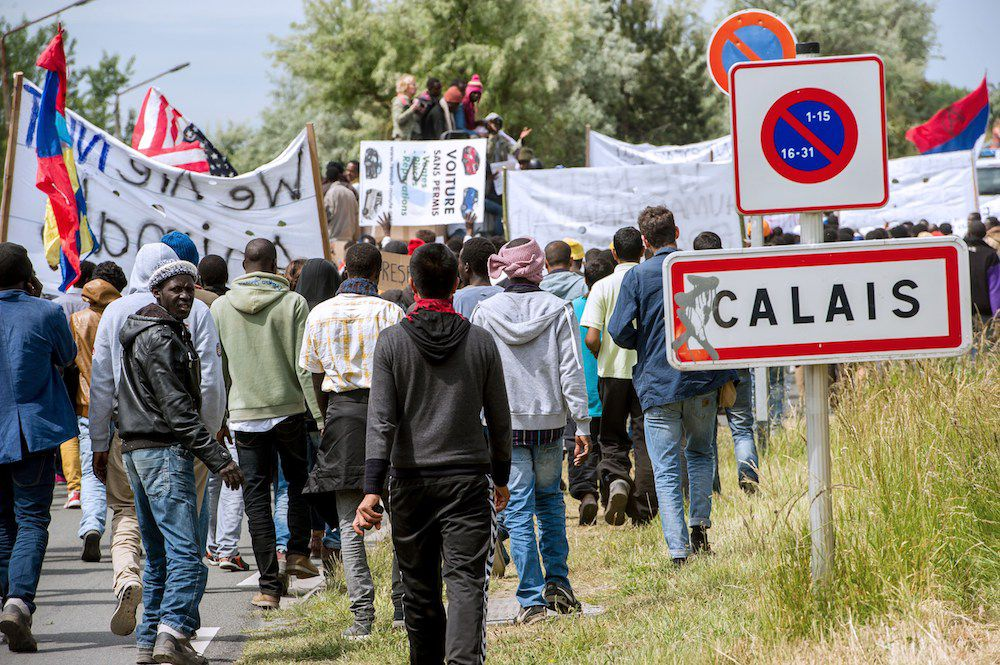 People hold banners during a demonstration of migrants in Calais, northern France, on World Refugee Day on June 20, 2015. AFP PHOTO / PHILIPPE HUGUEN