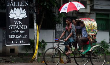"A man using a JICA emblazoned umbrella rides the back of a cycle rickshaw past a banner that reads ""We stand with the bereaved"" in a street near an upscale restaurant which was the site of a bloody siege that ended in the death of seventeen dead foreigners and five Bangladeshis, including two policemen, in Dhaka on July 5, 2016. Bangladesh's home minister said the attackers who stormed the upmarket cafe on the night of July 1, taking dozens of diners hostage and killing 20, were highly educated and from wealthy families. / AFP / ROBERTO SCHMIDT        (Photo credit should read ROBERTO SCHMIDT/AFP/Getty Images)"