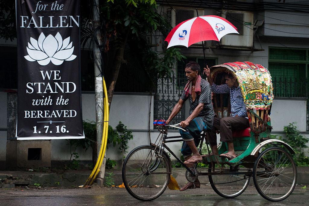 """A man using a JICA emblazoned umbrella rides the back of a cycle rickshaw past a banner that reads """"We stand with the bereaved"""" in a street near an upscale restaurant which was the site of a bloody siege that ended in the death of seventeen dead foreigners and five Bangladeshis, including two policemen, in Dhaka on July 5, 2016. Bangladesh's home minister said the attackers who stormed the upmarket cafe on the night of July 1, taking dozens of diners hostage and killing 20, were highly educated and from wealthy families. / AFP / ROBERTO SCHMIDT        (Photo credit should read ROBERTO SCHMIDT/AFP/Getty Images)"""